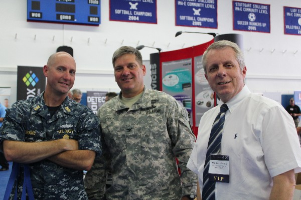 Previewing exhibits during the Summer Tech Expo VIP walk in July are (l-r) Command Master Chief Richard O'Rawe, USN, senior enlisted adviser for the Defense Information Systems Agency-Europe; Col. John Stack, USA, U.S. Army Garrison Stuttgart commander; and Roger Carpenter, chapter president.