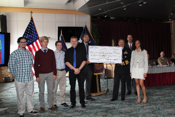 Adm. Martoglio (3rd from r), Tony Walk (4th from r), project manager, GDIT BICES Europe, and Milford (2nd from r) present a $2,500 check, provided by GDIT, to be divided evenly amongst the chapter�s scholarship recipients (l-r) Diego Williams, Olaf Bergeson, Matthew Watson, Dylan Rehwaldt, and Morgan Mahlock.