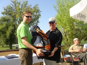 Jason Makowski (l) accepts one of the raffle items he won from Dr. Joseph Page Jr., chapter secretary and scholarship event organizer, at the September Golf Classic, which benefitted the chapter's scholarship fund.