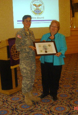 During the March meeting, Kathleen Miller (r), director for procurement, Defense Information Systems Agency, accepts a plaque from Col. Michelle Fraley, USA, chapter president, for her continued support of the chapter.