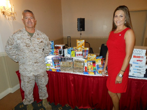 Col. James Turner, USMC, chapter president, and Mary Allison Yourchisin, chapter second vice president, stand next to school supply items collected by the Young AFCEANs at the September luncheon.
