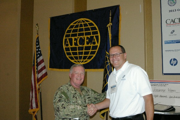 In April, Capt. Gerry Slevin, USN, chapter president, congratulates Chad Fisher, former publicity chair, for his dedication to the publicity role within the chapter.