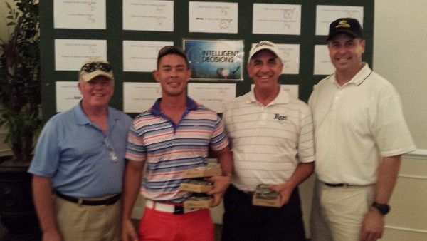 Capt. Slevin (l) presents golf trophies to tournament winners at the August event, which raised scholarship funds.
