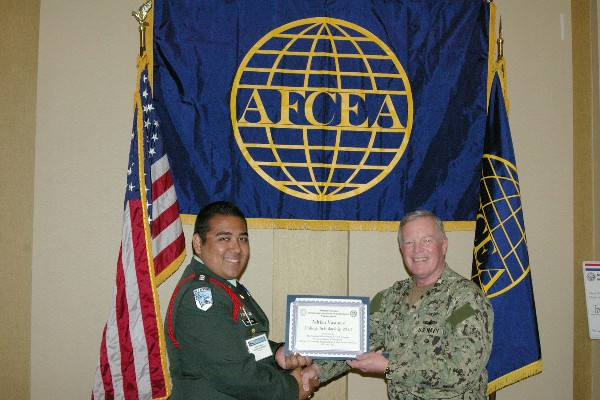 Capt. Gerry Slevin, USN, chapter president, presents a STEM Scholarship certificate to a student recipient in April.
