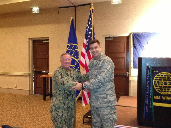 TAMPA-ST. PETERSBURG- Capt. Gerry Slevin, USN, chapter president (l), greets Col. Michael Hill, USAF, deputy director, communications systems, J-6 for Headquarters, United States Special Operations Command, speaker for the July luncheon.