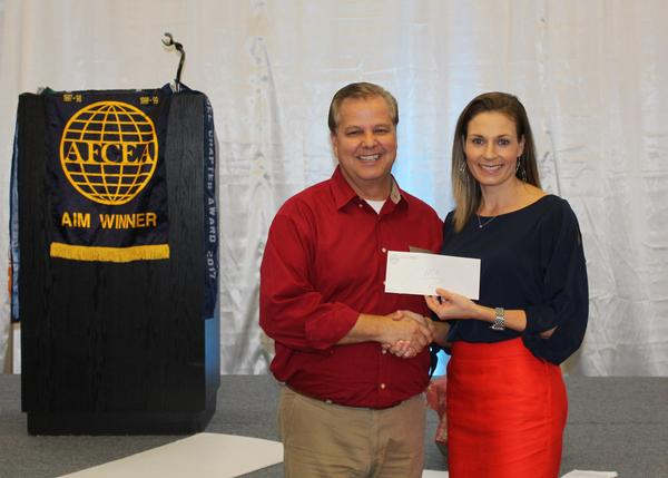 Young AFCEAN Chair Mary Allison Yourchisin (r) presents a check to Hope Children's Home Director Dr. Mike Higgins in December.
