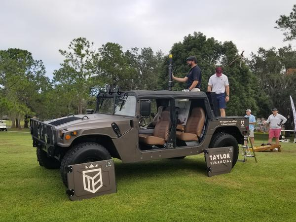 Taylor Financial, sponsor of the golf cannon, arrives at the November event with their Humvee.