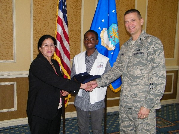 In September, Col. Glenn Powell, USAF (r), chapter vice president, presents Teresa M. Salazar with a chapter polo shirt, which she then presented to Cameron Mays, the local Mini Unmanned Aerial Vehicle (UAV)Competition winner.