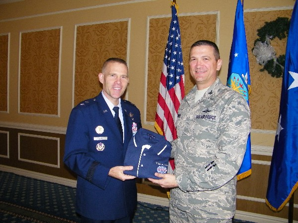 In December, Col. Glenn Powell, USAF (l), chapter vice president, presents a chapter polo shirt to Maj. Gen. Steven Kwast, USAF, director of requirements, Headquarters Air Combat Command, Joint Base Langley-Eustis, Virginia.