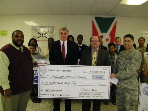 Maj. Rolando Aguirre, USAF (r), program lead for Adopt-A-School and member of the chapter�s board of directors, presents a $2,000 check in April to Deon Garner (l), assistant principal of Lindsay Middle School, while industry representatives John Dahlgren and Jeff Rowell of MITRE Corporation stand by.