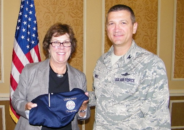 Chapter Vice President Col. Glenn Powell, USAF, presents June luncheon speaker Carroll McGillin, Cisco Systems, with a chapter polo shirt.
