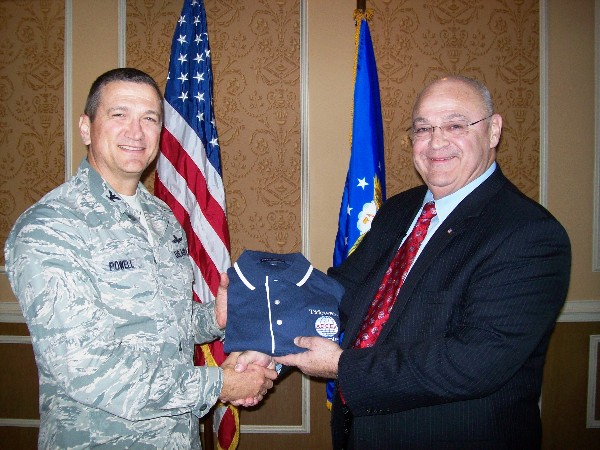 Col. Glenn Powell, USAF (l), chapter president, presents Dr. Albert Mitchum Jr., the political adviser to the commander of Air Combat Command, with a chapter polo shirt following his speech at the November meeting.