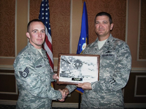 Col. Glenn Powell, USAF (r), chapter president, presents a chapter plaque to Staff Sgt. James Brown, USAF, AFCEAN of the Month for October.