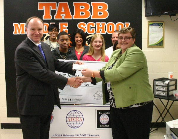 William Travis (l), vice president, communication services, Bosh Global Services, presents a $5,000 grant to Antonia Fox, Tabb Middle School principal, in November.