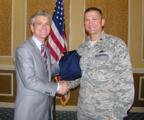 Chapter President Col. Glenn Powell, USAF (l), presents Rep. Scott Rigell (D-VA) with a chapter shirt for speaking at the May luncheon.