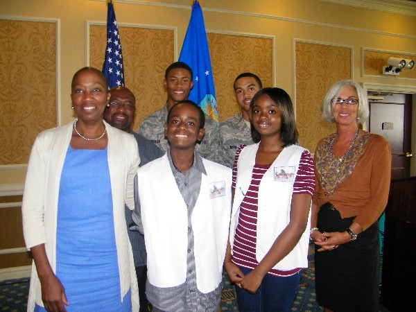 "Mays (front row, 2nd from l), winner of a local mini unmanned aerial vehicle competition, is recognized in September with support from his sister Mercedes (front row, 2nd from r), who is also a member of the ""Stepping Up America"" aviation and robotics program. Also on hand for the presentation are Dr. Angela Goodloe (l), director of Stepping Up America; Rhonda Richardson (r), chapter STEM UAV lead; and chapter event judges (back row, l-r) William Benson, Airman 1st Class Braxton Ward, USAF, and Airman 1st Class Corey Kinsler, USAF."