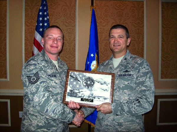 In November, Col. Powell (r) presents the November AFCEAN of the Month plaque to Tech. Sgt. Alan Pickford, USAF.