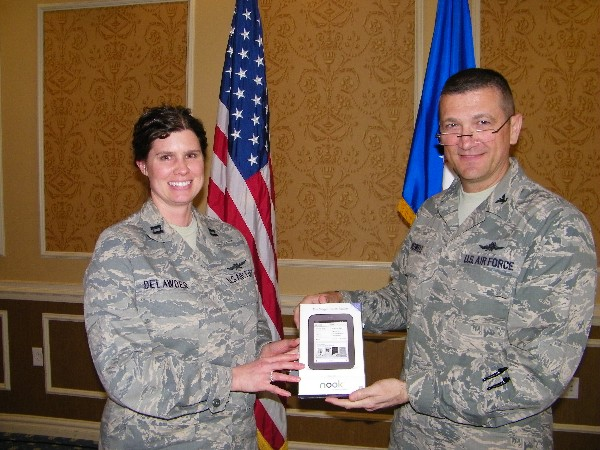 Capt. Colleen Delawder, USAF, 10th Intelligence Squadron, receives a Nook e-reader from Col. Powell that was given away during scholarship raffle at the March luncheon.