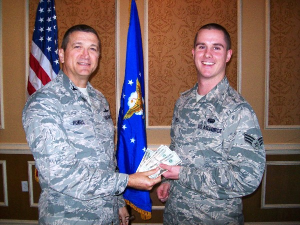 Senior Airman Jacob Bell, USAF (r), 633rd Communications Squadron, takes home the $80 jackpot from the membership drawing presented by Col. Powell in November. This drawing is held each month with the pot starting at $10 and grows each month by $10 until there is a winner.