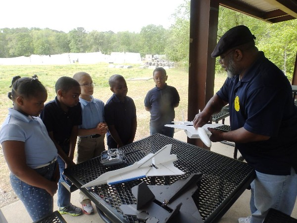 Aaron Mills of the 480th Intelligence, Surveillance and Reconnaissance Wing explains the aerodynamic effects of lift, drag, thrust, weight and balance to (l-r) Ryan Mack, Isaiah Irving, Maleik Waldo, Jayden Perry and Naphish Washington in May.