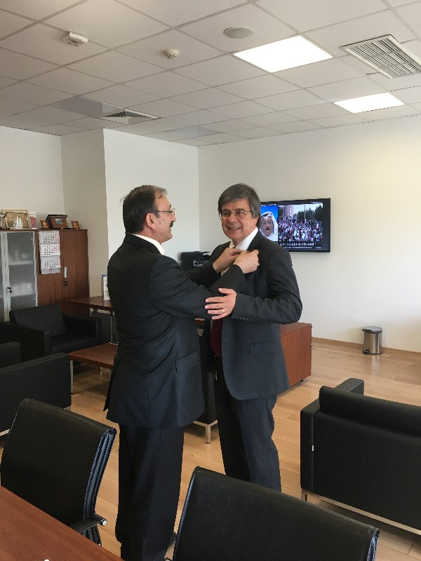 Chapter President Kamil Zafer Seljuk (l) secures Y. Suat Bengur's lifelong membership pin to his lapel in May.