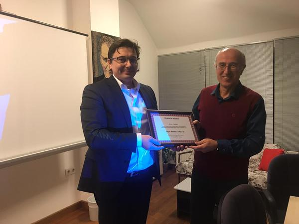 Tanju Karagoz, chapter secretary (l), presents the certificate of appreciation to guest speaker Mehmet Topcu at the chapter's April meeting.