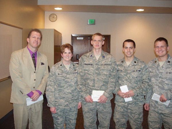 Lt. Col. Karilynne Wallace, USAF, commander, and Martin present ROTC scholarships in January to Air Force ROTC cadets Jacob Singleton (c), Samuel Von Niederhausern (2nd from r) and Jordan Woods, all students at Utah State University.