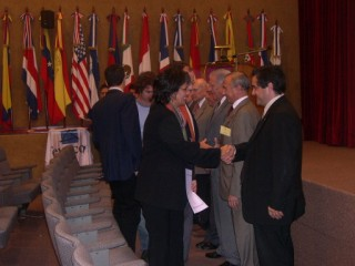 Magister Eng. Luis Valle, coordinator, giving a certificate to attendee Eng. Moira Callegare, National Commission of Communications. To his side is the Eng. Luis Favotto, coordinator,  giving other certificate to attendee Eng. Gustavo Barragán, head of Barragán SA entreprise