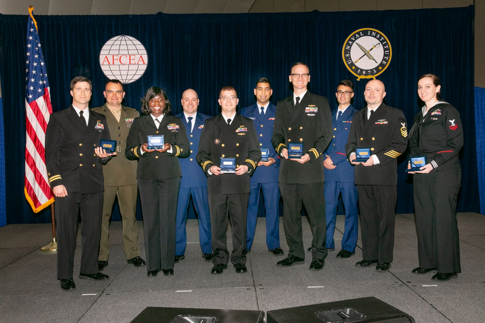 Copernicus Winners pose with their awards in front of a dark blue curtain with the logos of AFCEA and the U.S. Naval Institute and the American flag at WEST 2019